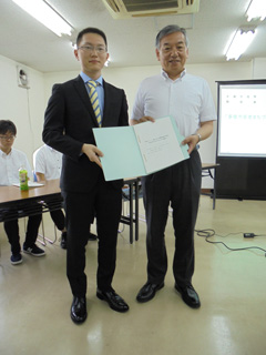 阿部裕行多摩市長に報告書手渡す馬場明仁さん(経営情報学部2年)